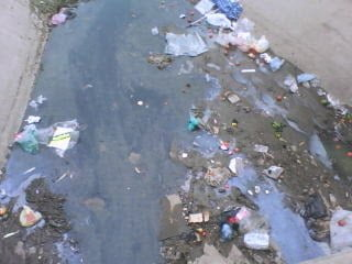 Ejemplo de contaminación lineal, producto de los desechos que se arrojan a un canal de aguas grises que posteriormente contaminará una fuente hídrica.